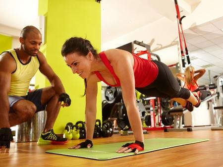 Mulher desportiva que faz o treinamento de suspensão TRX com personal trainer na academia. Imagens