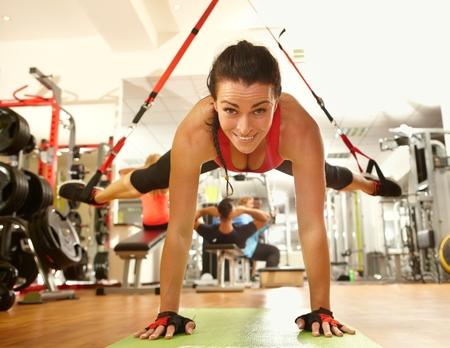 Gelukkige vrouw genieten van harde TRX schorsing training in de sportschool.