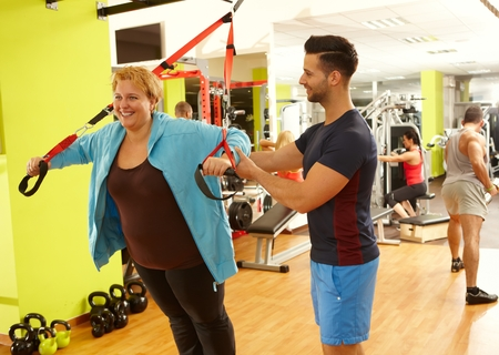personal trainer: Overweight woman doing suspension training with the guidance of personal trainer. Stock Photo