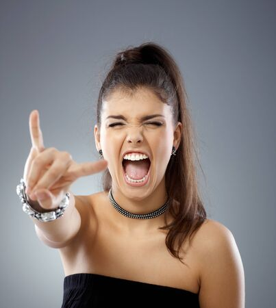provocative women: Provocative girl shouting eyes closed, showing rock on hand gesture.