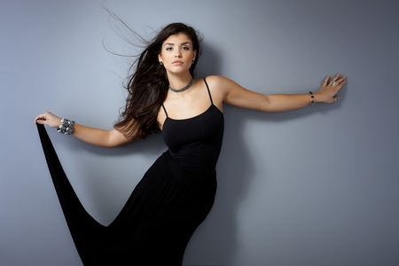 outspreading: Beautiful sensual woman posing by grey wall with long windtorn hair and black dress.