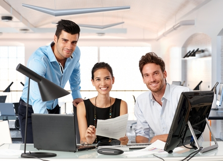 woman at work: Happy team of young business people working together in office. Stock Photo