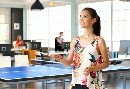 table tennis: Attractive young woman playing table tennis in office. Stock Photo