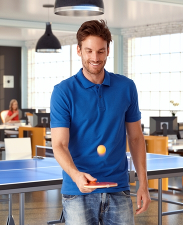 Young man playing table tennis in office, smiling. Banque d'images