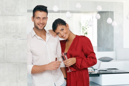 young couple smiling: Attractive young loving couple smiling at luxury home.
