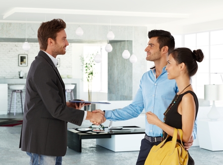 real estate business: Young couple and real estate agent shaking hands, smiling. Side view. Stock Photo
