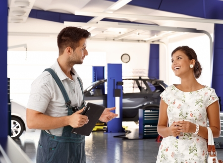 auto service: Happy female customer talking to car mechanic in auto repair shop, smiling happy.