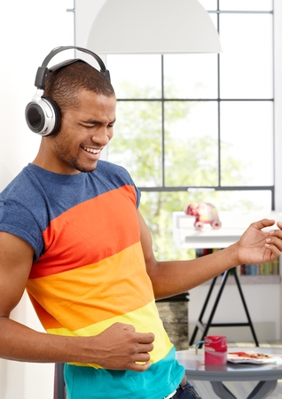 pretending: Young black man enjoying music through headphones eyes closed, pretending to play a guitar.