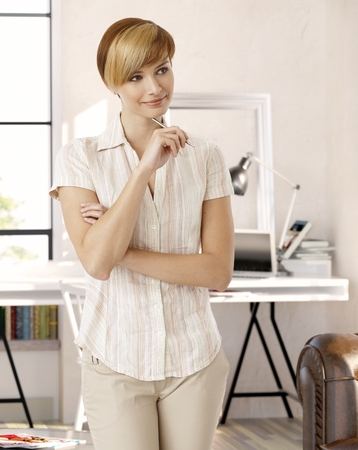 gingerish: Young blonde woman standing in study at home, holding pen, smiling, looking away.