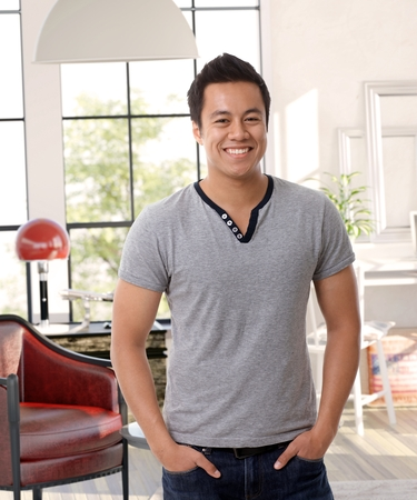 Portrait of happy smiling Asian man standing hands in pockets in old-fashioned living room.