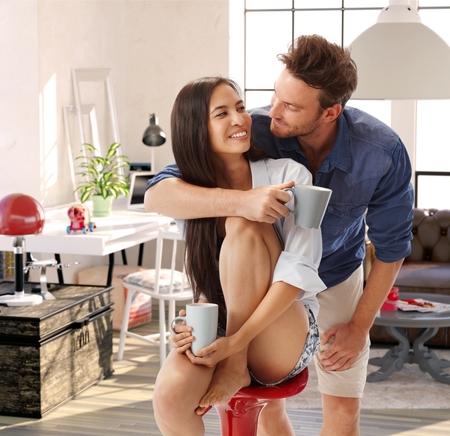 parejas enamoradas: Feliz abrazando pareja amorosa, sonriendo en casa.