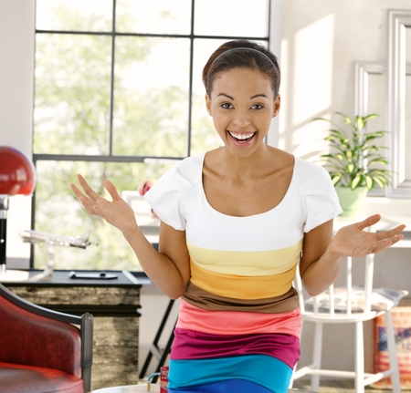 outspreading: Young afro-american woman laughing happy with arms wide open, looking at camera at home.