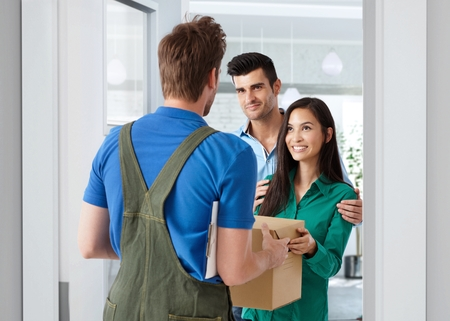 deliveryman: Young couple receiving package from delivery-man at home.