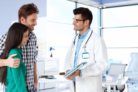 若いカップルの笑みを浮かべて、医者と相談します。横から見た図。