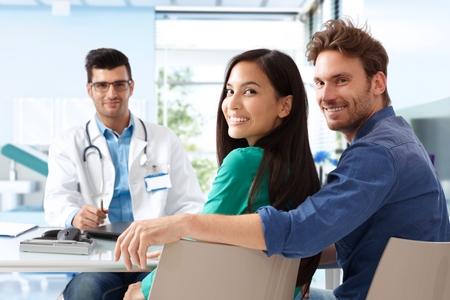Casal jovem e atraente feliz sentada na sala do médico na consulta.