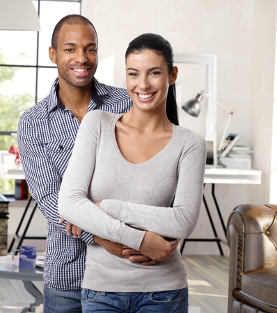 Happy young interracial loving couple hugging and smiling at home, looking at camera.