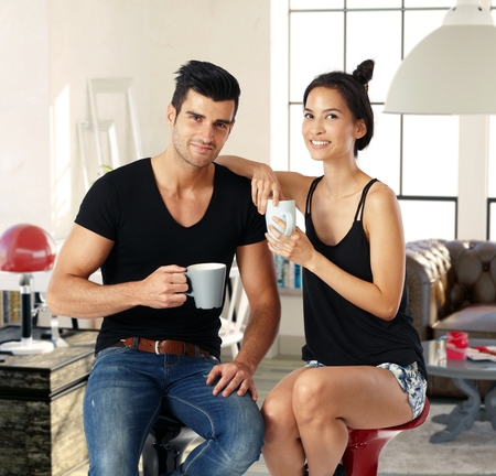 asian american: Happy young couple drinking tea at home, smiling, looking at camera. Stock Photo