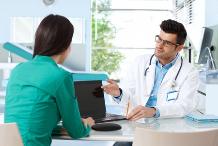 Doctor consulting with patient in doctors room, presenting results on laptop computer.