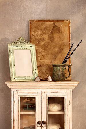 Vintage style home interior with show-case, frame and painting tools. photo