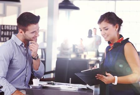 flight attendant: Businessman drinking coffee while secretary writing notes.