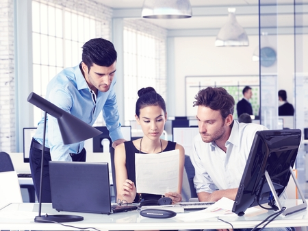 Young businesspeople sitting at desk, working together. Stock Photo