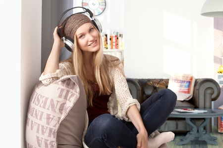tailor seat: Happy young girl listening to music through headphones at home, smiling, looking at camera. Stock Photo