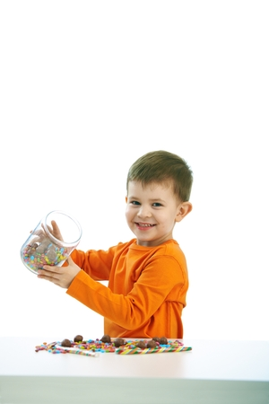 stockphoto: Happy child ( four years old little boy ) eating sweets, isolated on white background.