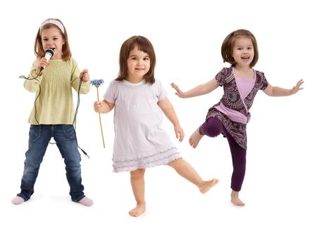 Drie schattige kleine meisjes dansen, zingen om de microfoon, plezier maken op een witte achtergrond.