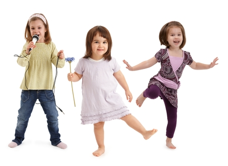 Three cute little girls dancing, singing to microphone, having fun over white background. Stock Photo