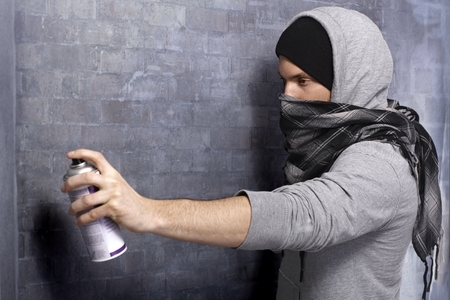 aerosol can: Graffiti man in hooded shirt and face mask spraying brick wall by aerosol can.