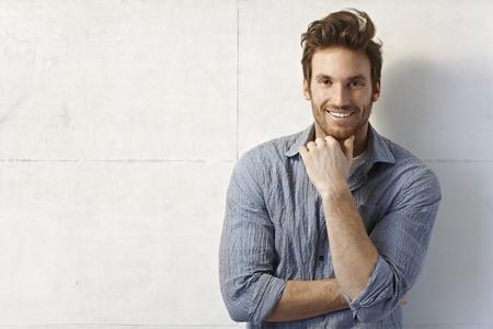 Portret van knappe jonge casual man glimlachend over muur.