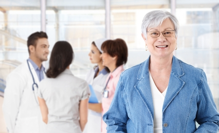 Portrait of happy elderly woman in glasses. Medical team in background. photo