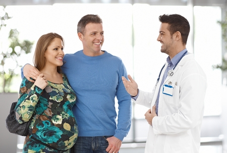 wife and husband: Young and cheerful pregnant couple talking to doctor at clinic. Husband and wife embrace each other.
