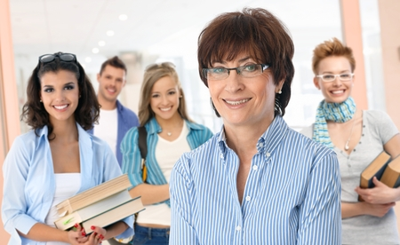 female teacher: Portrait of happy senior female teacher with group of students in background.