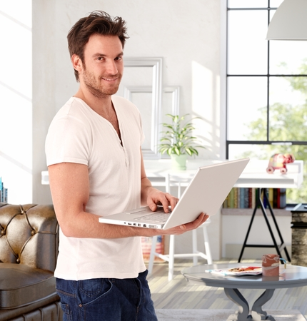 young unshaven: Handsome young man standing in living room at home, holding laptop computer, smiling.