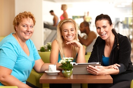 companionship: Happy female companionship sitting around table in gym coffee, resting, talking, looking at photos, smiling, looking at camera. Stock Photo