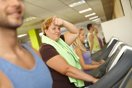 Exhausted fat woman training on running machine in gym.