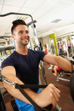 weight machine: Happy young man training in gym on weight machine. Stock Photo