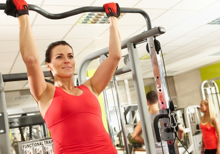 health club: Sporty woman doing hard pull-up workout in health club.