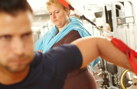 envious: Fat woman watching athletic man in fitness club envious. Stock Photo
