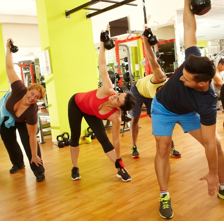 health club: Group of people doing fitness workout in health club.