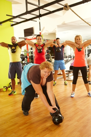 fails: Fat woman fails to lift up dumbbell in gym, doing fitness workout in group.