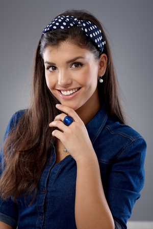 stockphoto: Pretty girl smiling with hand on chin, looking at camera.
