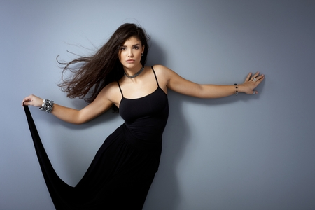 outspreading: Hot woman posing by grey wall in black dress with long windtorn hair.