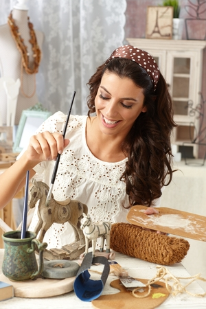 Young woman enjoying hobby painting in vintage style at old-fashioned home, smiling. Stock Photo