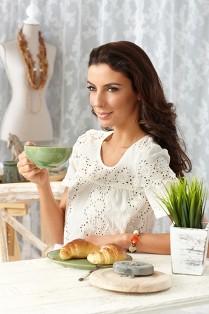 fantasize: Smiling young woman having breakfast tea and croissant at retro home.