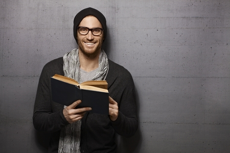 Happy urban style young man standing against grey wall, smiling, reading book, looking at camera. Stockfoto