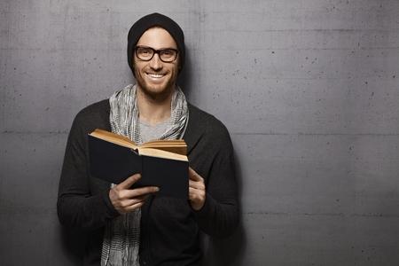 Heureux style urbain jeune homme debout contre le mur gris, souriant, livre de lecture, regardant la caméra.