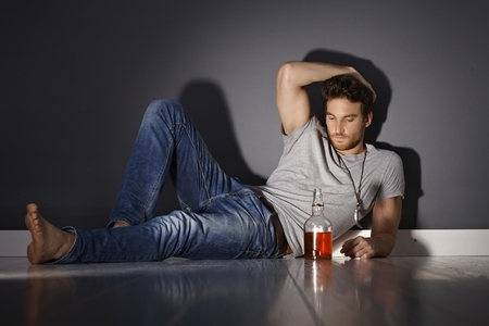 depressed man: Depressed young man lying on floor, drinking alone.