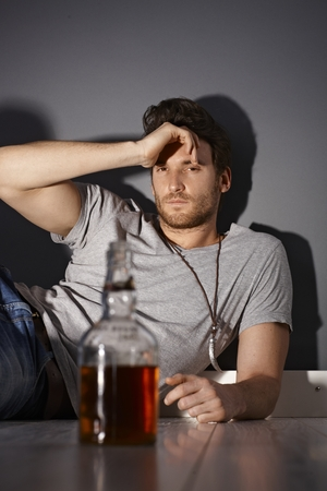 stubble: Depressed young man drinking whiskey.